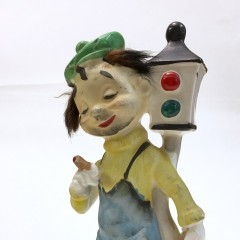 Ceramic bum leaning against two-section traffic light
