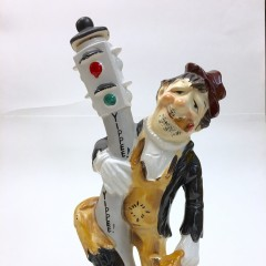 """Ceramic decanter of bum haning on to traffic light, says """"Yippee!"""""""