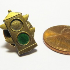 Flat brass two section traffic light pin with painted green indication